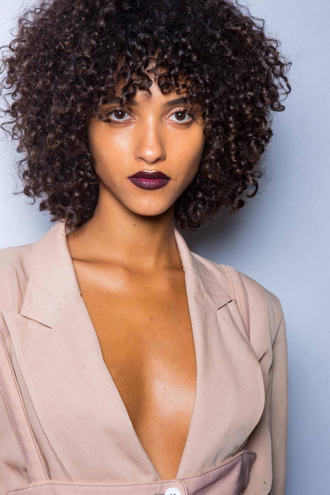 curly hair type quiz: backstage shot of model with curly hair, wearing suit and dark lipstick