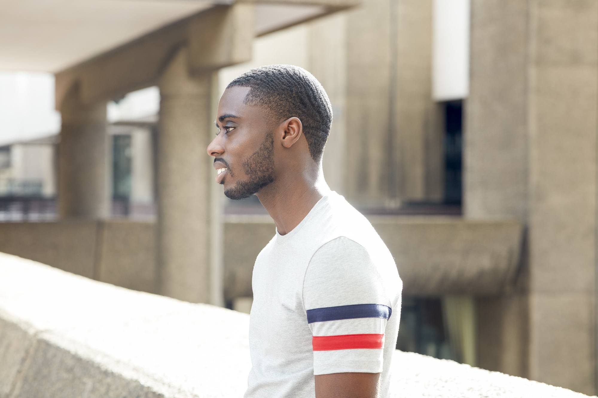 Hairstyles for men with thin hair: Outdoor shot of a man with 360 waves, wearing a white tshirt with blue and red stripes on the arm