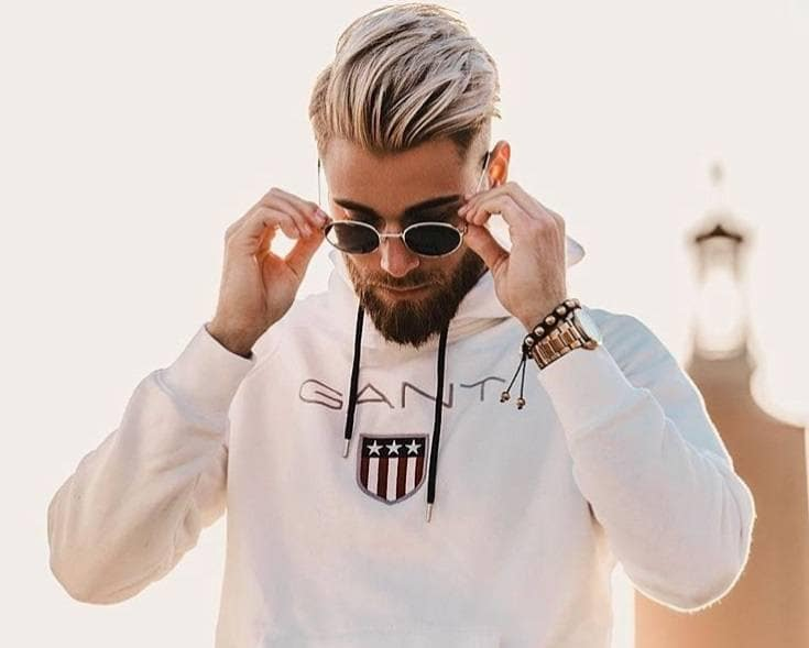 Men's haircuts for round faces: Man with a round face with a white blonde choppy quiff, wearing sunglasses and a Gant branded jumper with sunglasses, posing outside