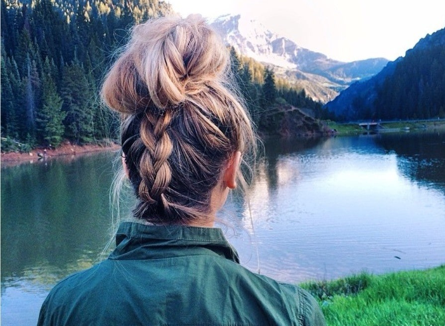 Braided updos for long hair: close up shot of woman with long hair styled into a upside down braid updo bun hairstyle