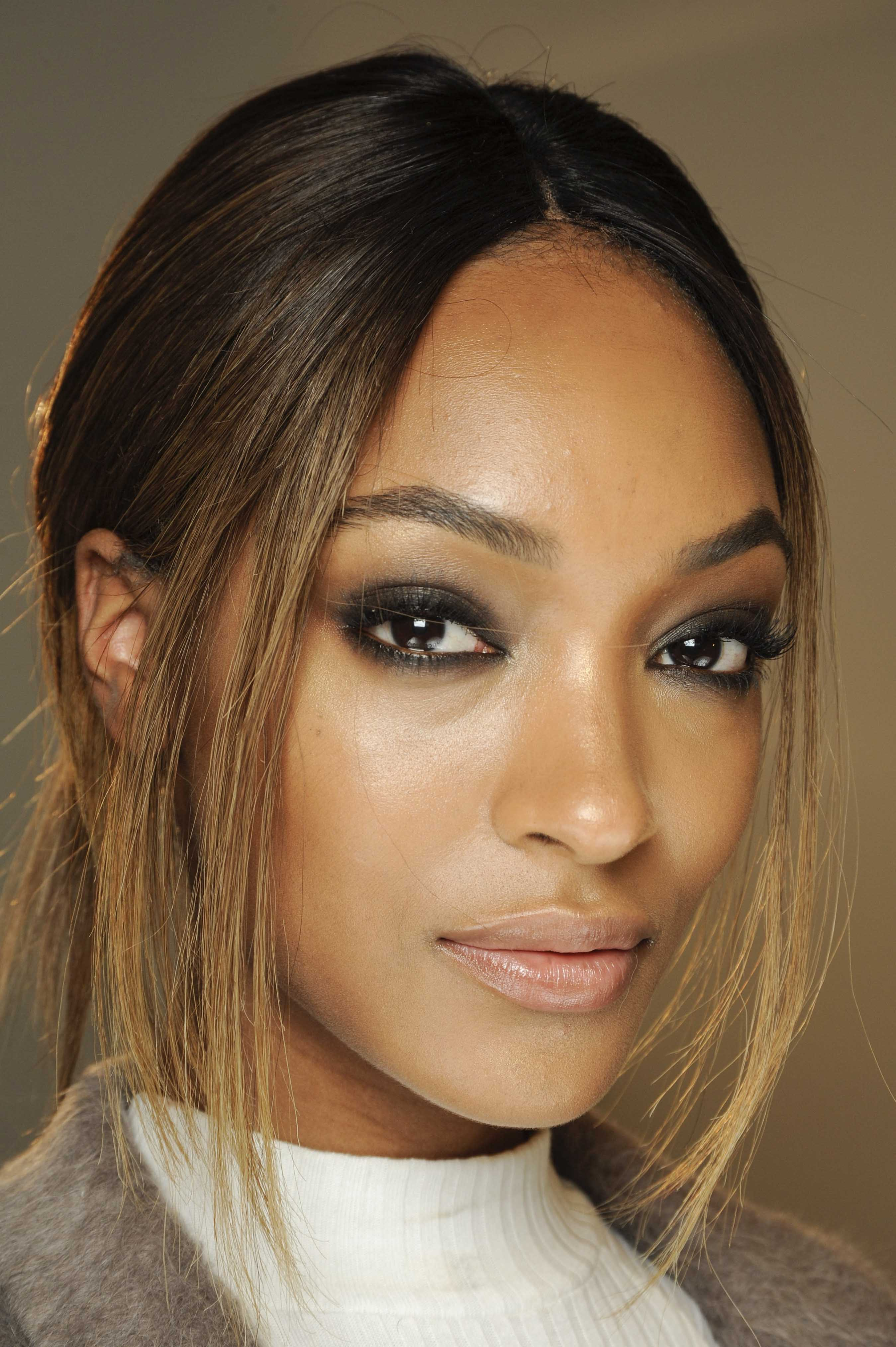 Balayage technique: Jourdan Dunn with dark golden brown balayage hair in low ponytail with dark eye make-up, and high neck top.