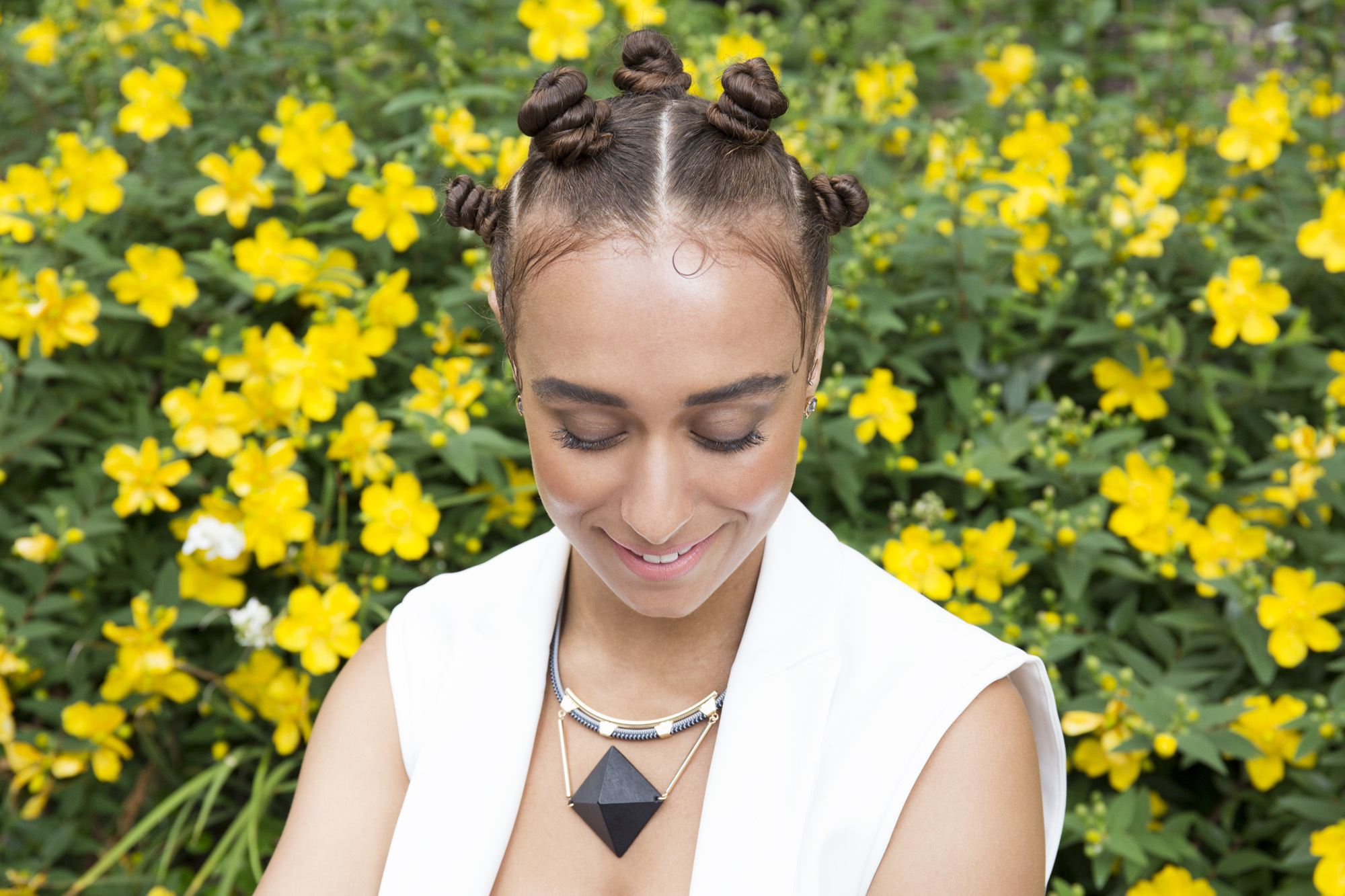 Low manipulation hairstyles: Close up shot of women with bantu knot hairstyle posing in a field of yellow flowers
