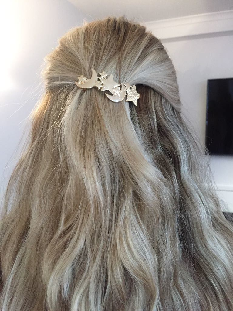 back view of beth with blonde half-up, half-down wavy hair with star hair trend slide