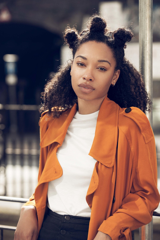 Low manipulation hairstyles: Close up shot of black model with half up bantu hairstyle, wearing orange coat and white shirt, street style shot