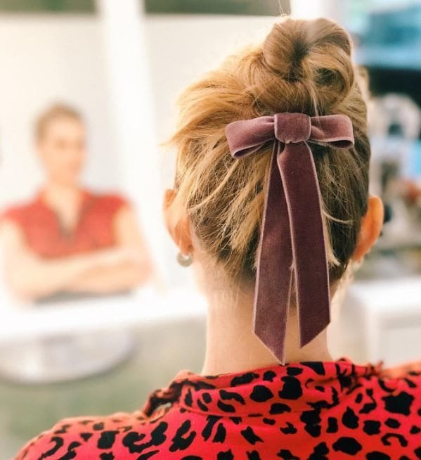 Woman with dark blonde hair styled into a high bun with pink velvet bow under bun