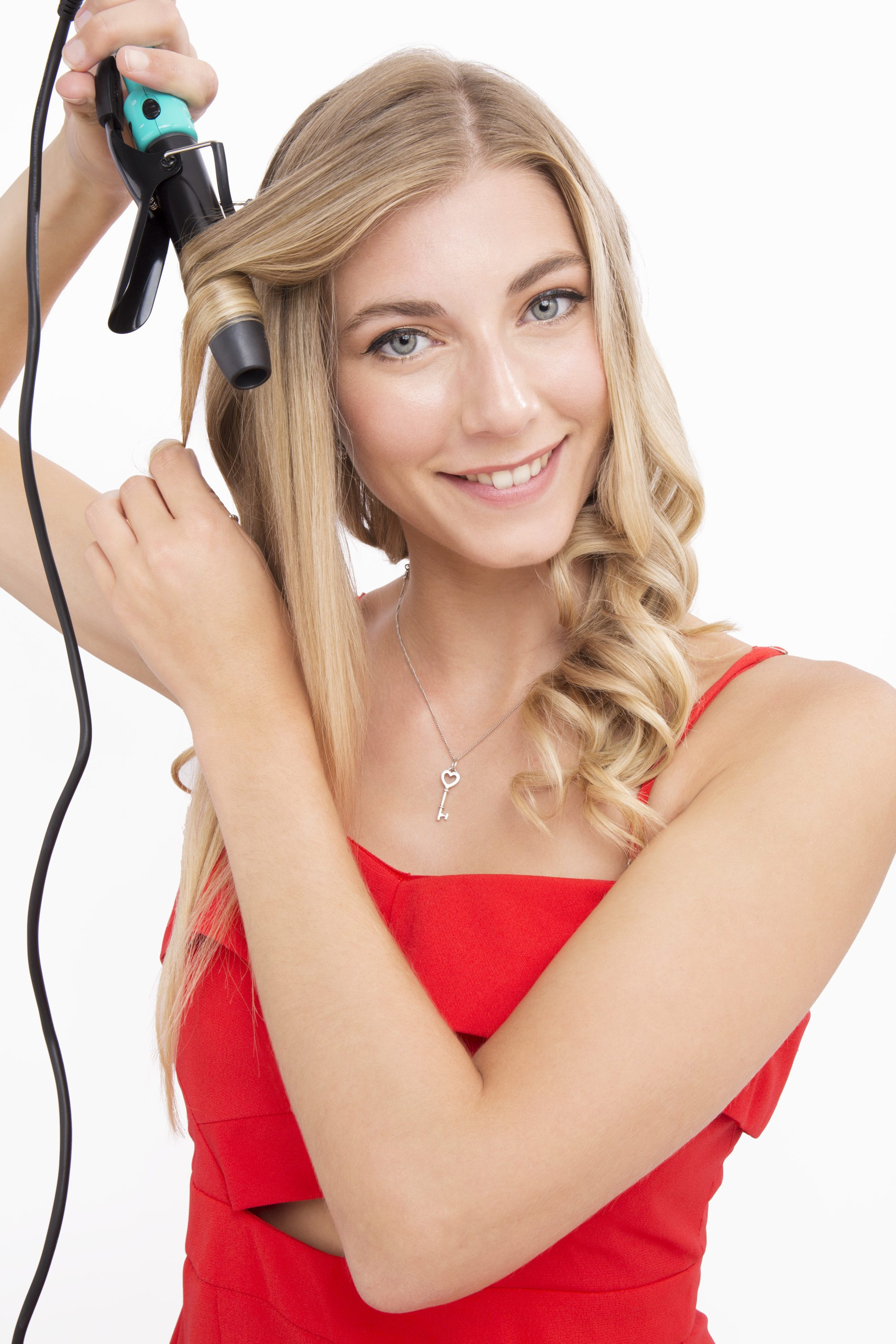 blonde model in a red jumpsuit using a curling tong to curl her hair