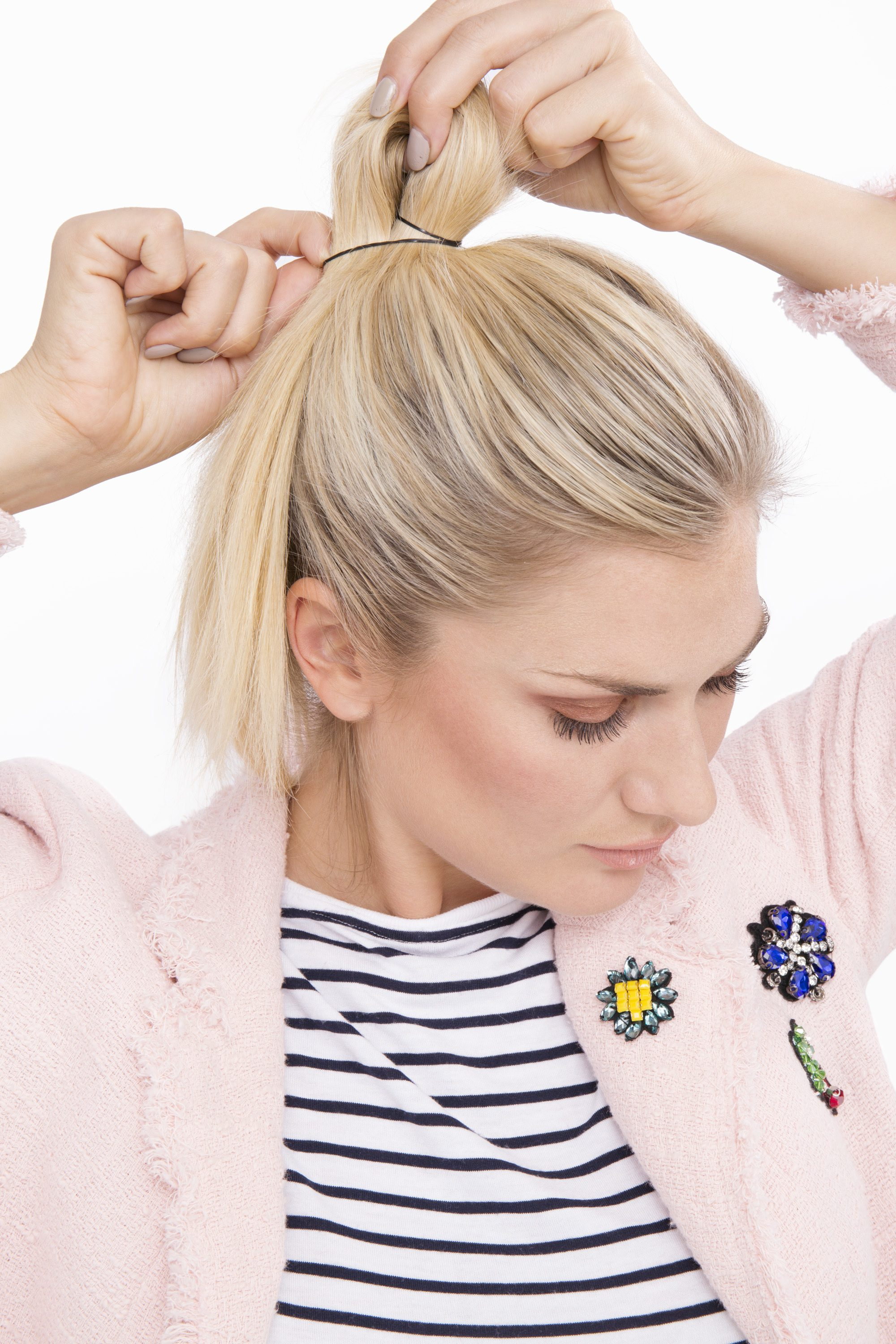 blonde model tying her hair into a ponytail