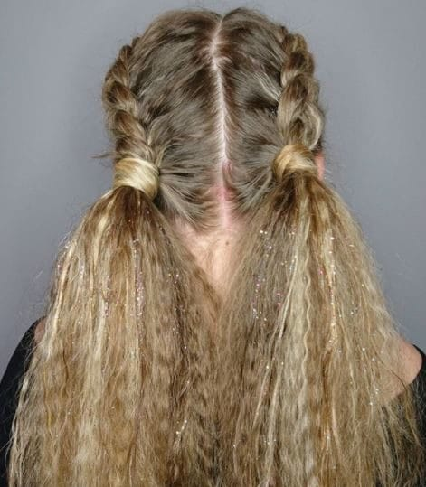 Crimped hair: Woman with long crimped blonde hair styled in two french braids.