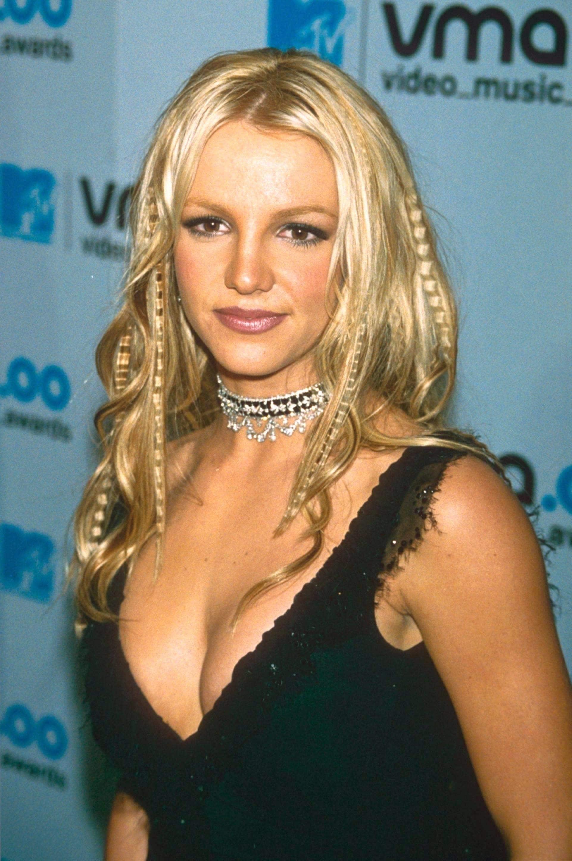 Crimped hair: Britney Spears with blonde medium length wavy hair wearing a black dress at MTV VMAs.