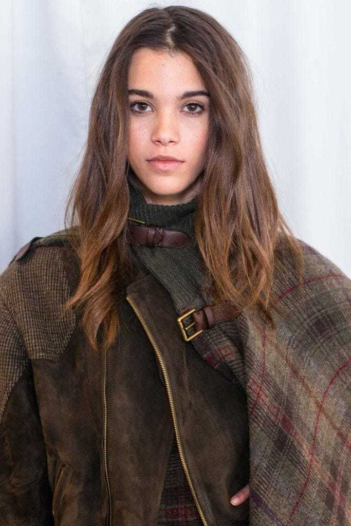 Balayage technique: Woman with dark brown medium length balayage hair wearing a checked coat.