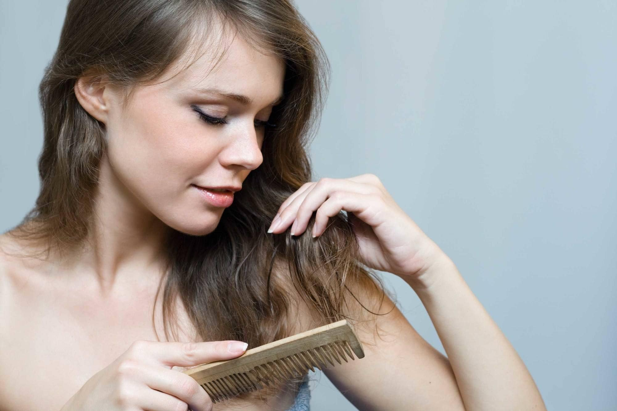 close up shot of woman using a detangling comb through her hair, in a studio