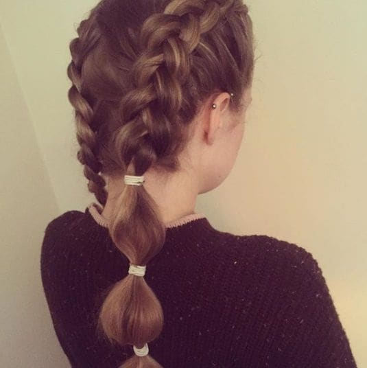 brunette woman with her hair in two boxer braids with bubble ponytail ends