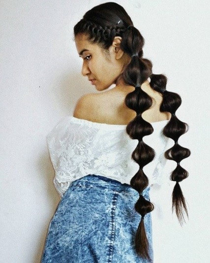 back view of a woman with long brunette hair in two bubble ponytail pigtails