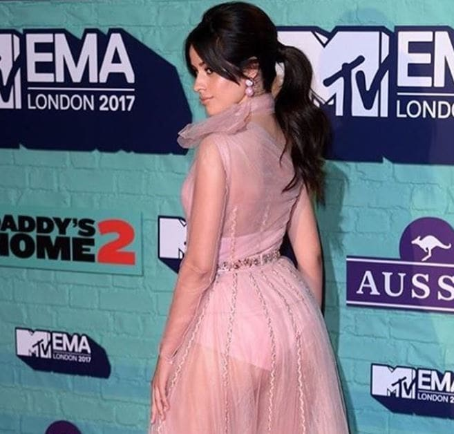 Side view of Camila Cabello with dark hair in 60s inspired bouffant ponytail and bardot bangs at the 2017 MTV EMAs
