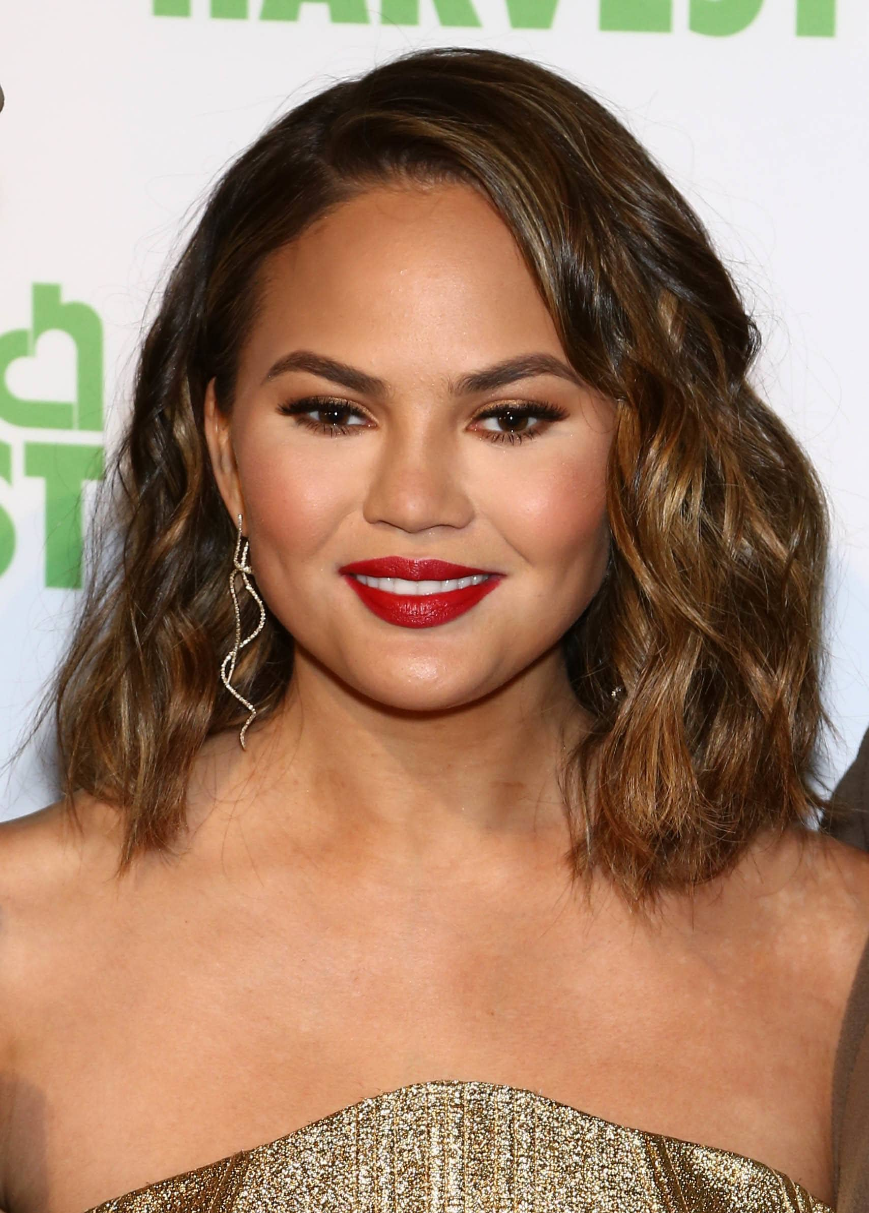 front view of chrissy teigen with dark brown balayage golden brown curly long bob