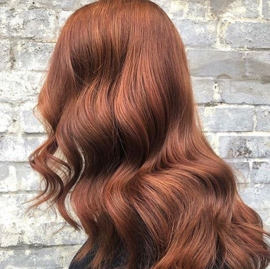 Cinnamon hair colour: Side shot of a woman with cinnamon brown hair styled into a loose Hollywood waves.