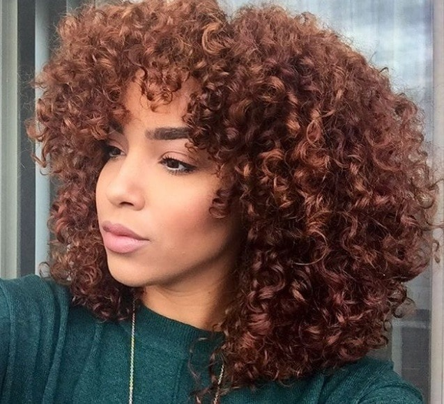 Cinnamon hair colour: Close up shot of a woman with medium, natural cinnamon curls.