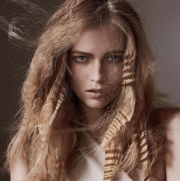 Crimped hair: Model with tousled crimped waves on long blonde hair.
