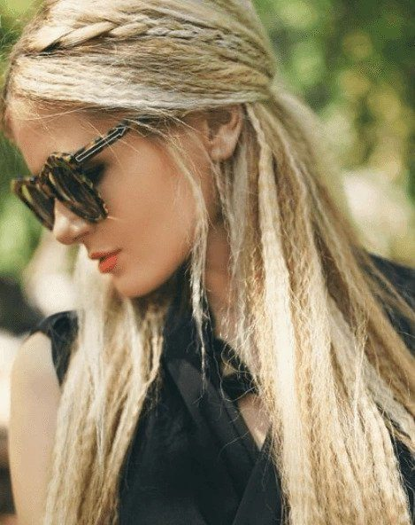 Crimped hair: Woman with long blonde crimped hair in half-up, half-down finish wearing dark sunglasses.