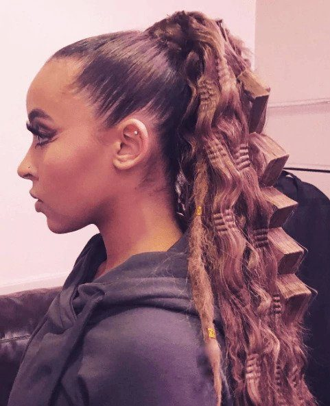 Crimped hair: Woman with long brown hair in high ponytail with large crimped waves wearing a hooded top.