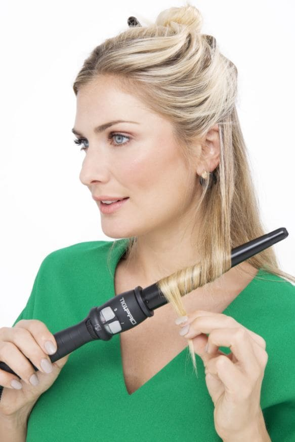 blonde model curling hair with curling wand