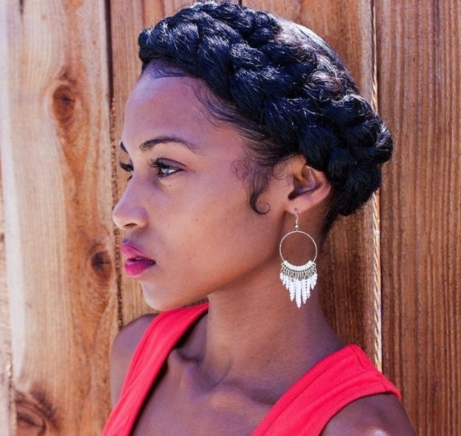protective hairstyles for natural hair: close up shot of woman with halo braid hairstyle on natural hair, posing and wearing red lipstick