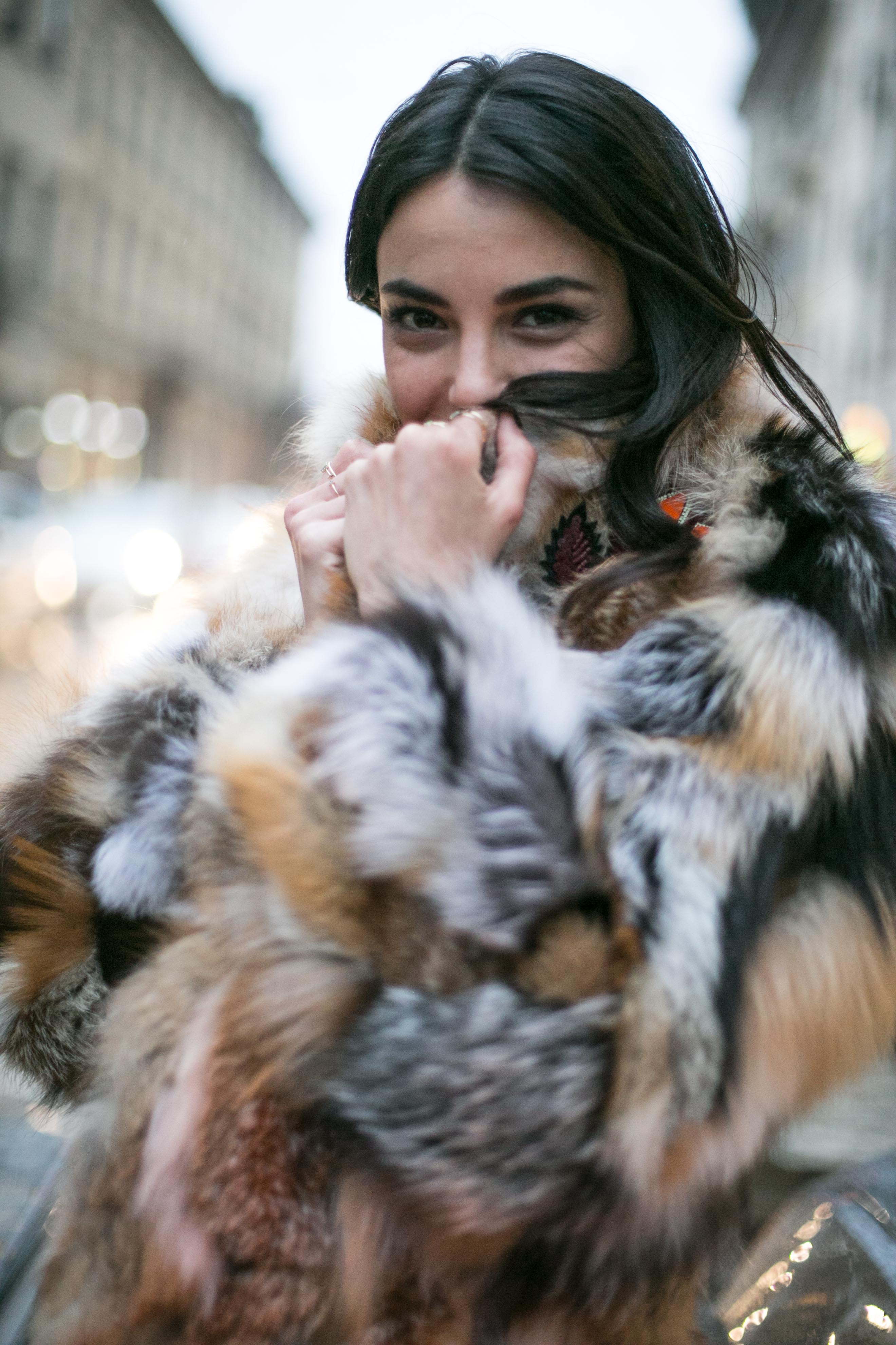 close up shot of woman with black hair, wearing faux fur jacket