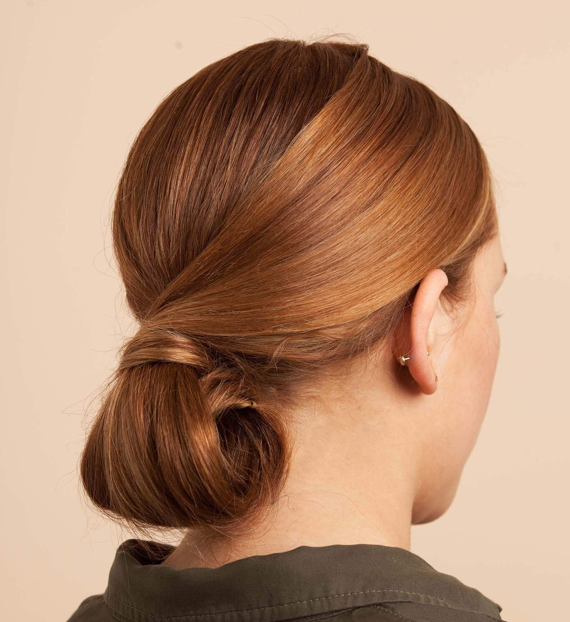 Party hairstyles: Woman with light golden brown straight hair in chignon updo bun tuck.