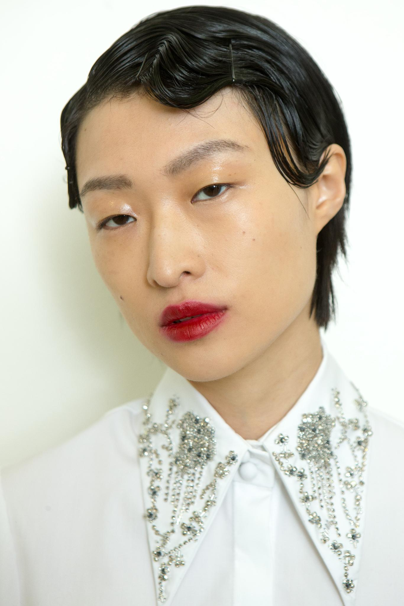 Christmas hairstyles: Asian model with short brown hair with finger waves detail along the hairline wearing a white shirt and red lipstick.