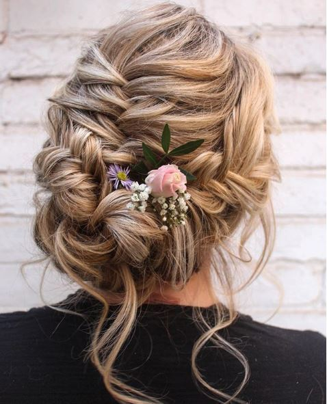 Fishtail braids: Woman with blonde highlighted hair in fishtail braids updo.