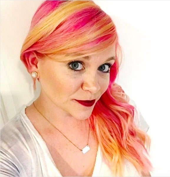 selfie of a woman with yellow and pink fruit salad inspired hair
