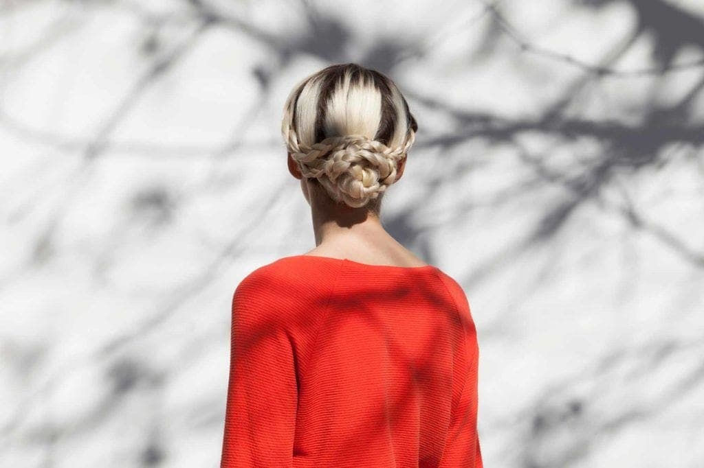 Party hairstyles: Woman with bleach blonde hair styled in a snake braid bun updo wearing a red top.