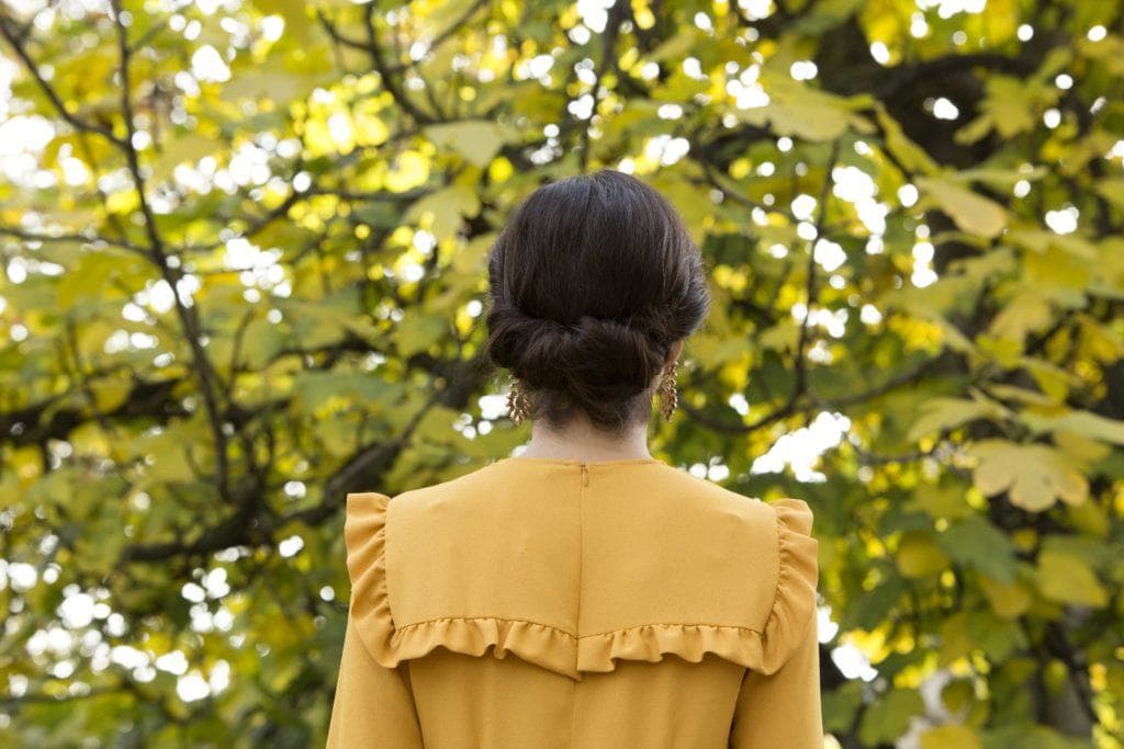 Party hairstyles: Woman with dark brown hair in gibson tuck updo wearing a yellow frill dress.