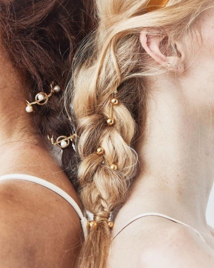 close up shot of a brunette and blonde woman with braided hair with beaded hair accessories woven in