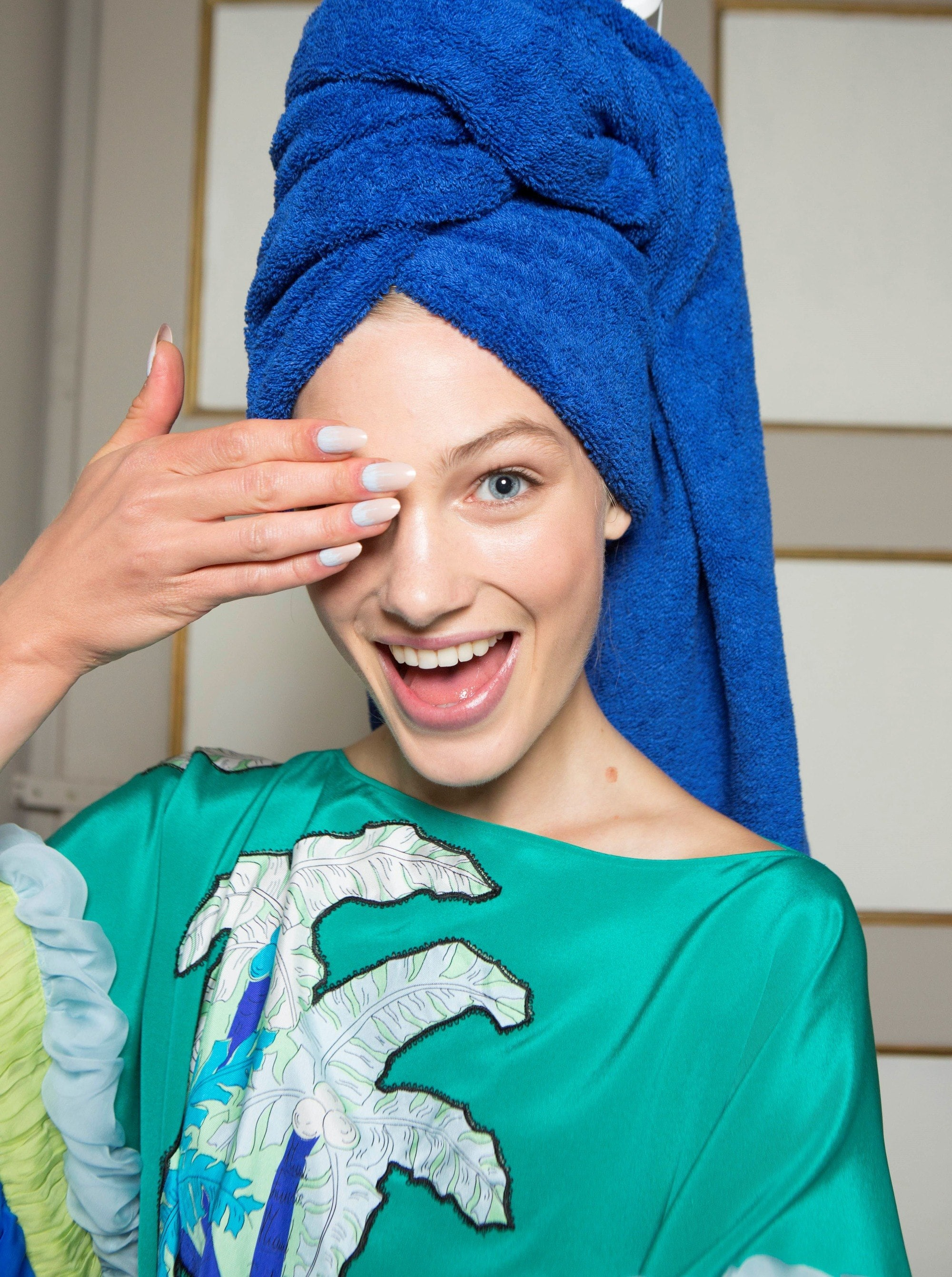 close up shot of woman with towel on her head, wearing blue dress and posing