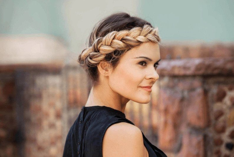 Party hairstyles: Woman with blonde long hair in halo braid updo wearing a black vest.