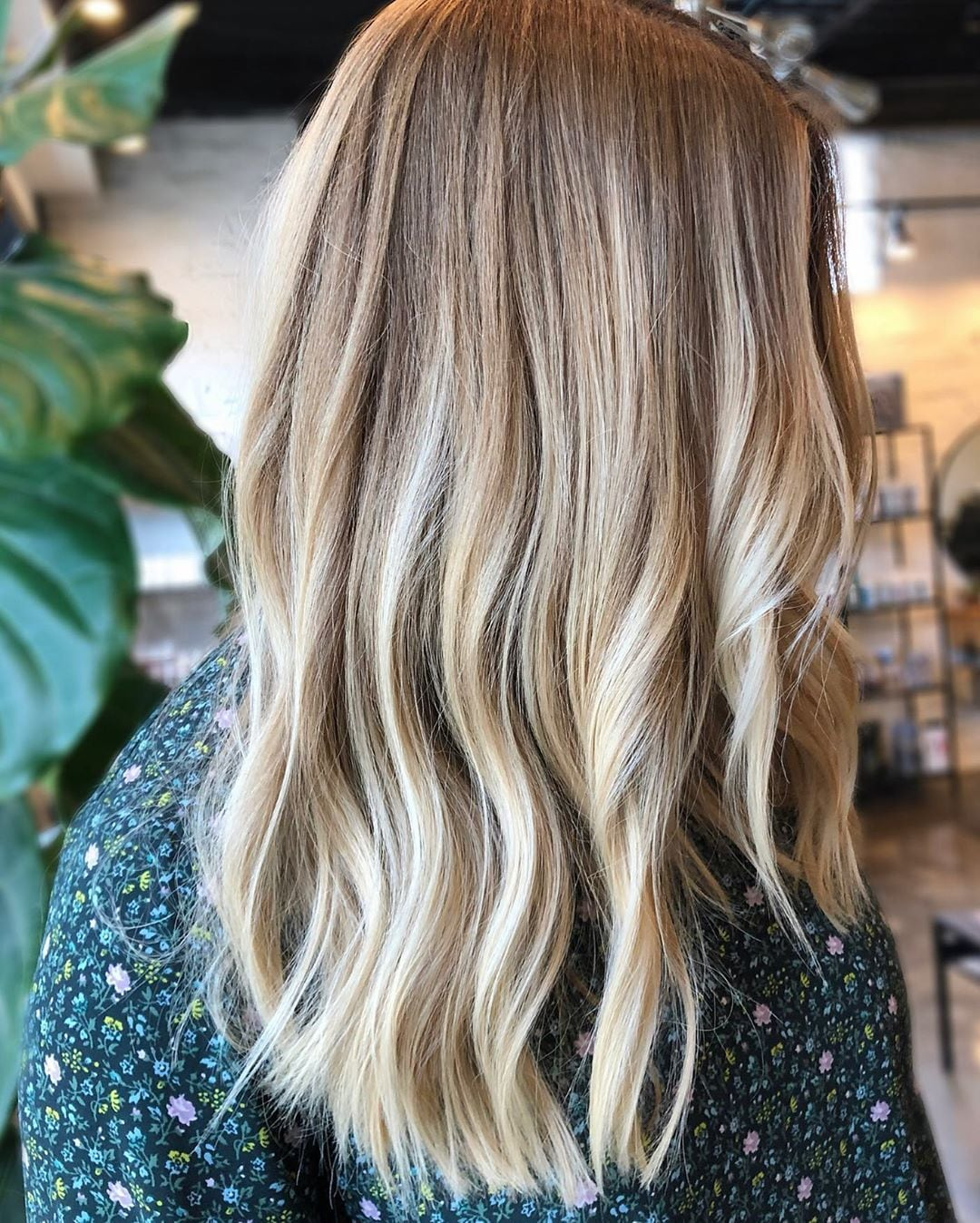 Woman with mid-length wavy honey blonde hair with light blonde highlights