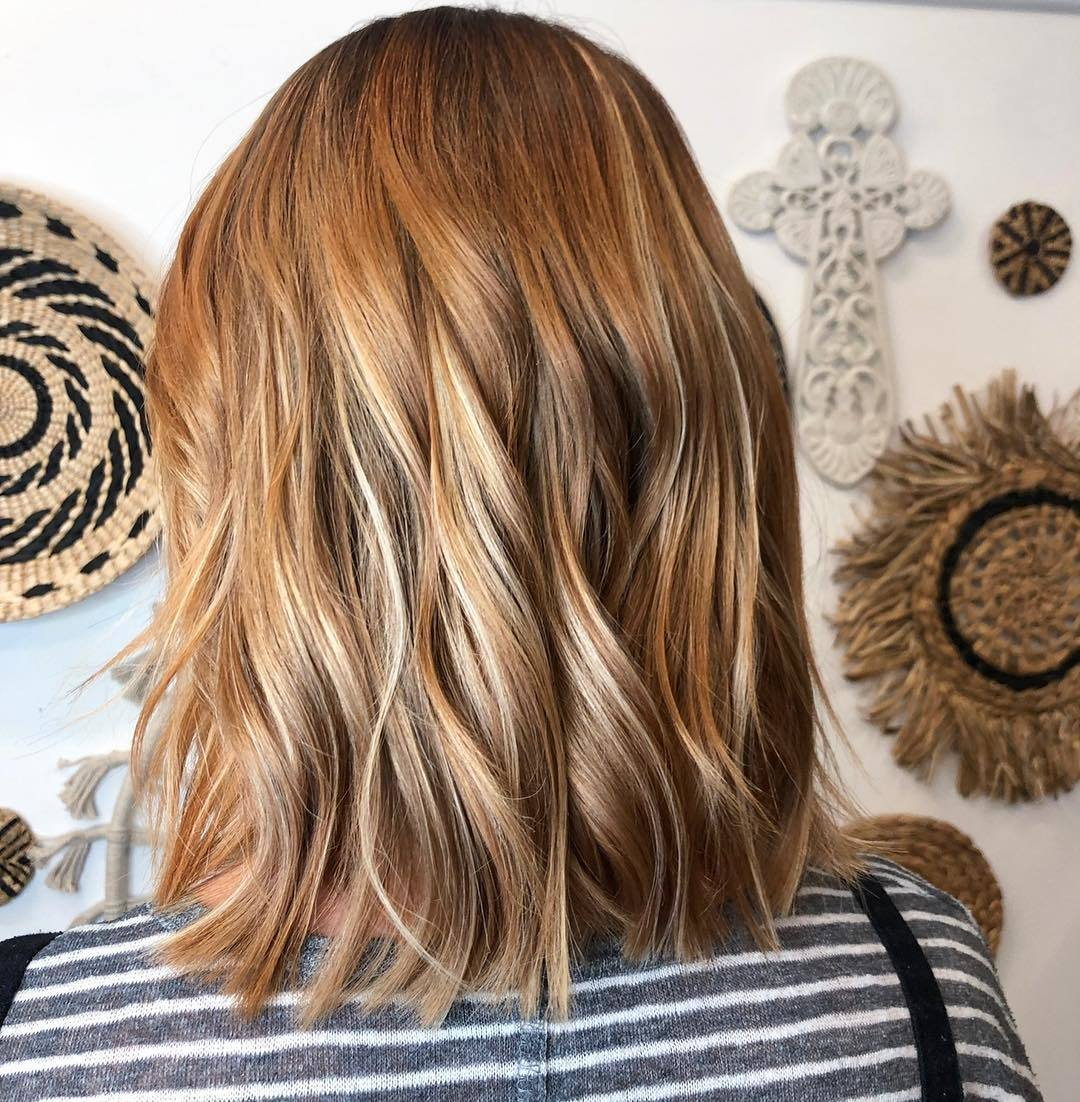 Woman with a light honey red wavy bob
