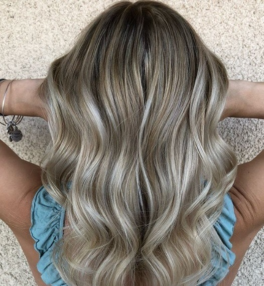 close up back shot of a woman with ash blonde babylights in her dark blonde hair, wearing a blue top and posing against a white background