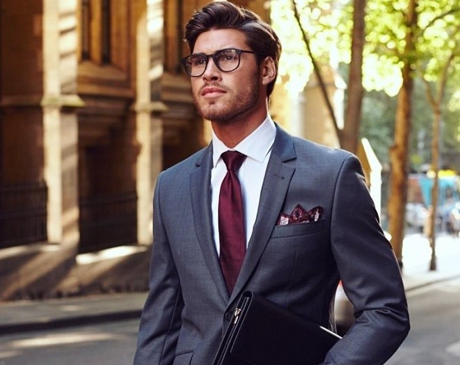 Men's haircuts for round faces: A man with a round face, with chocolate brown swept-back hairstyle wearing a suit and glasses, posing outside