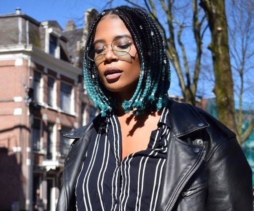 close up shot of woman with short bue ombre box braids, wearing leather jacket and black striped shirt with sunglasses, posing outside