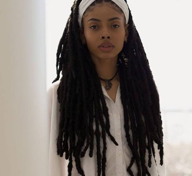 protective hairstyles for natural hair: close up shot of woman with long dreadlocks, wearing white headband and shirt, posing in a studio