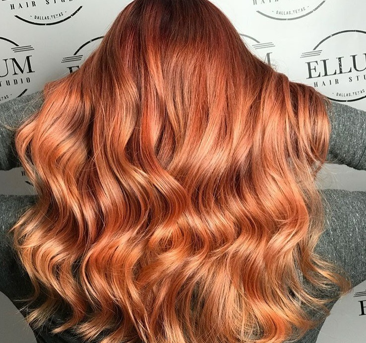 Cinnamon hair colour: Close up shot of a woman with wavy dark brown hair to cinnamon red ombre.