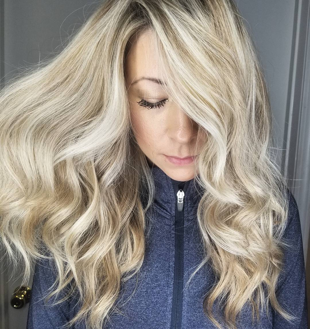 Woman with light honey blonde curly hair with a side parting