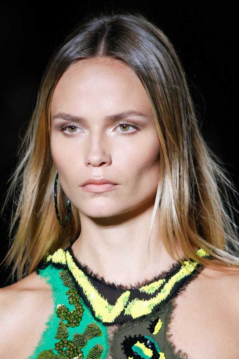 Balayage technique: Woman on runway with straight brown blonde balayage hair wearing a green dress.