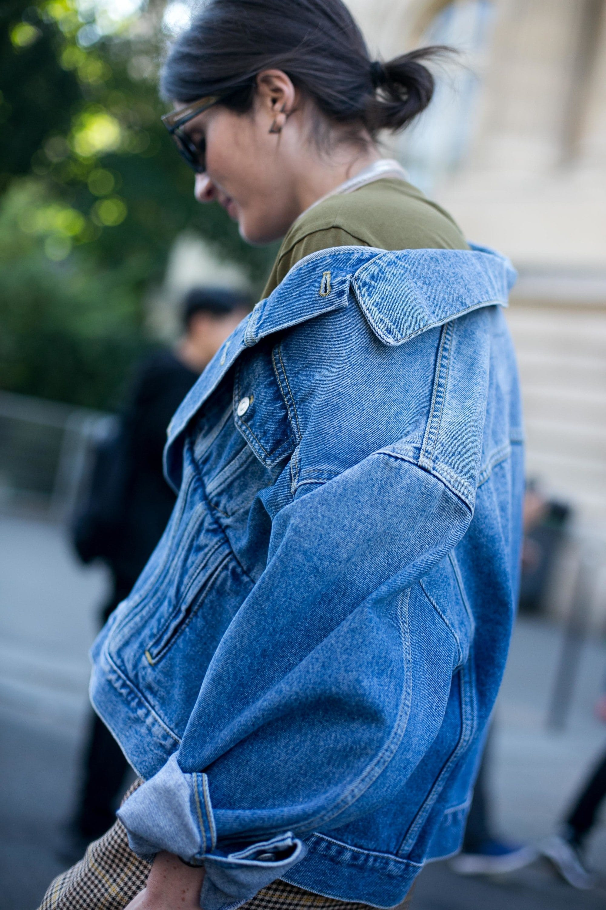 Windswept hair: Street style shot of a brunette woman with her hair in a messy bun wearing an oversized denim jacket