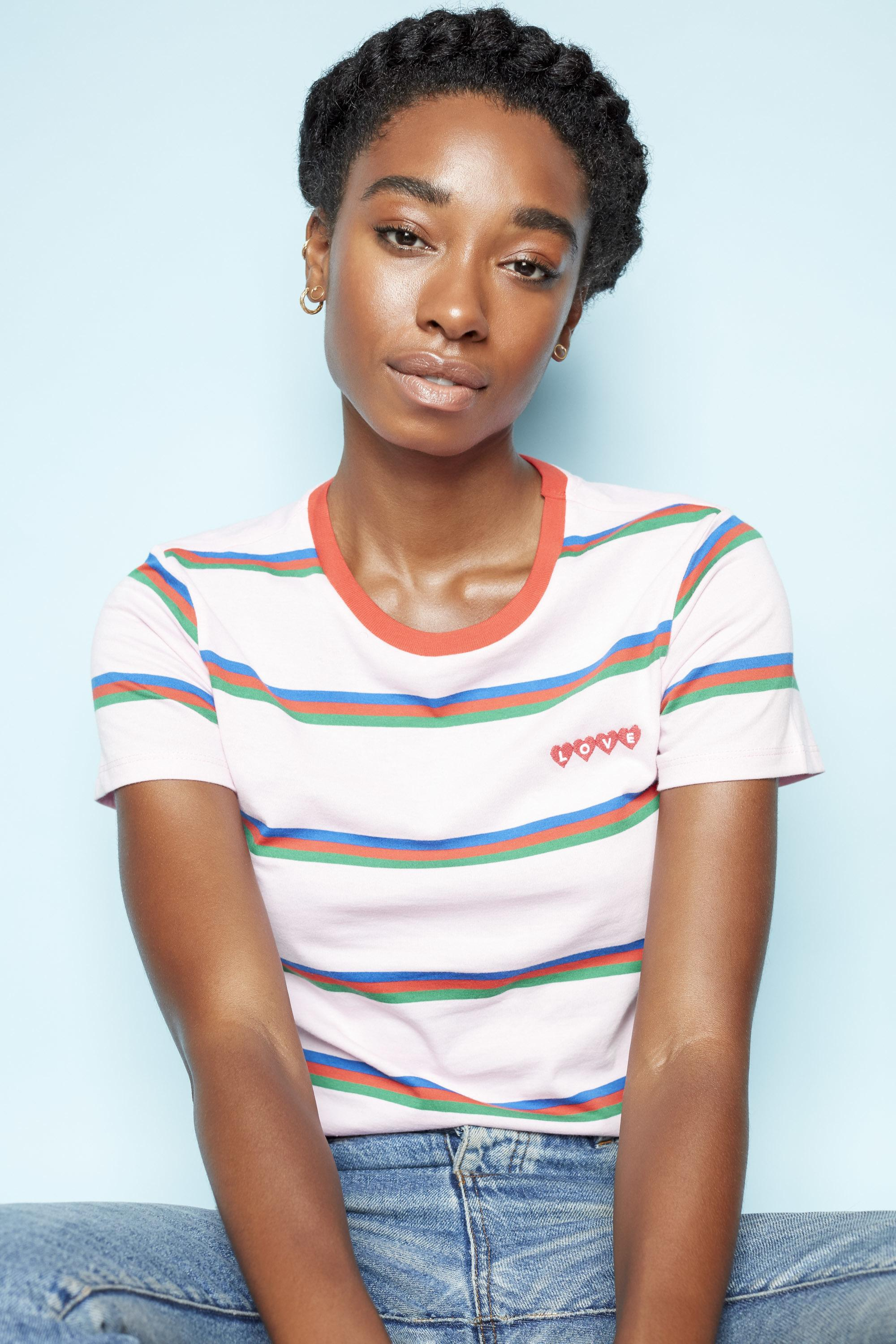 Low manipulation hairstyles: Photo of a young black woman with natural hair styled in a halo braid updo