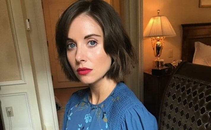 close up shot of alison brie with short hairstyle with blue denim dress, wearing red lipstick