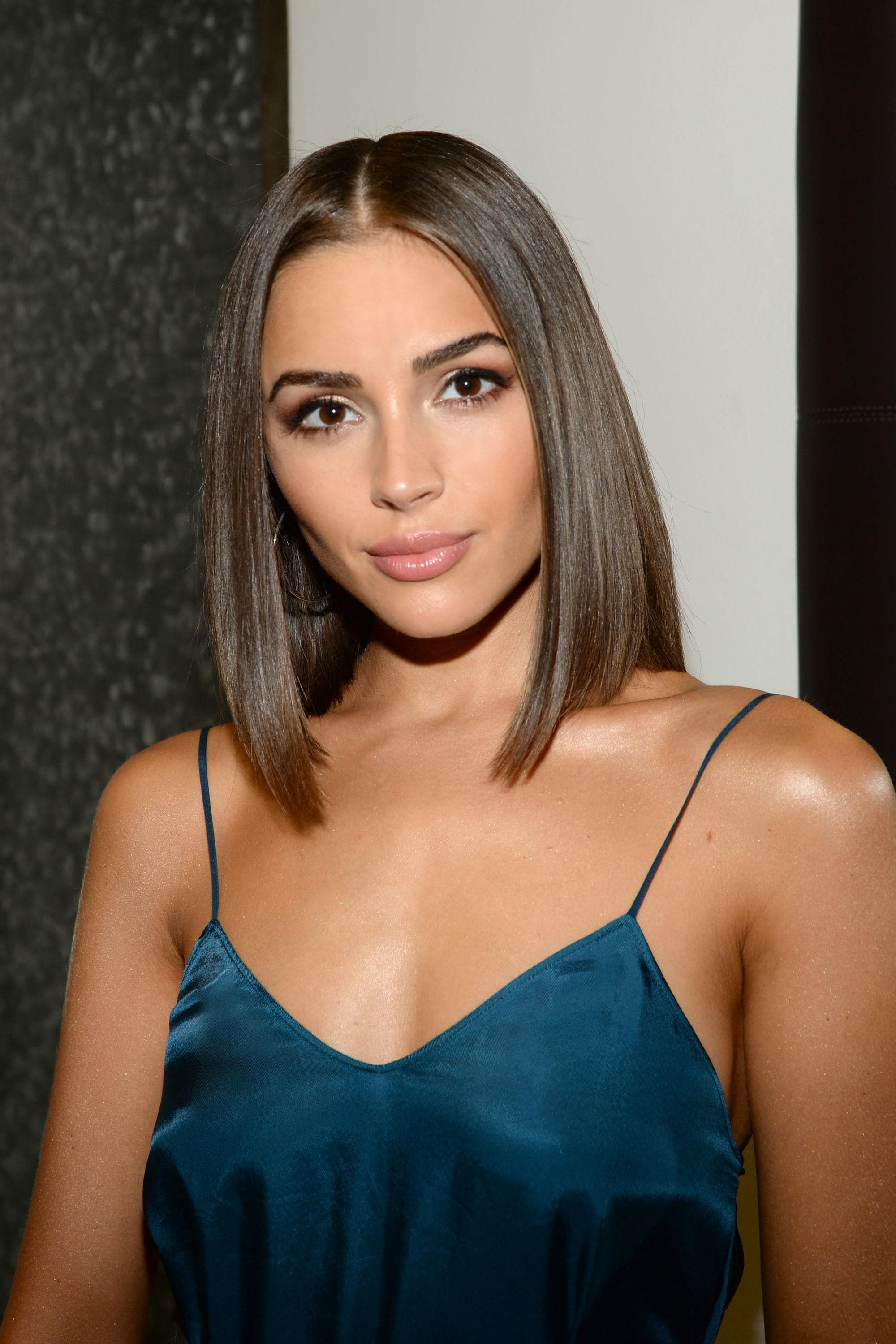 Haircuts for fine straight hair: Olivia Culpo with an A-line brunette bob, wearing a teal strappy dress
