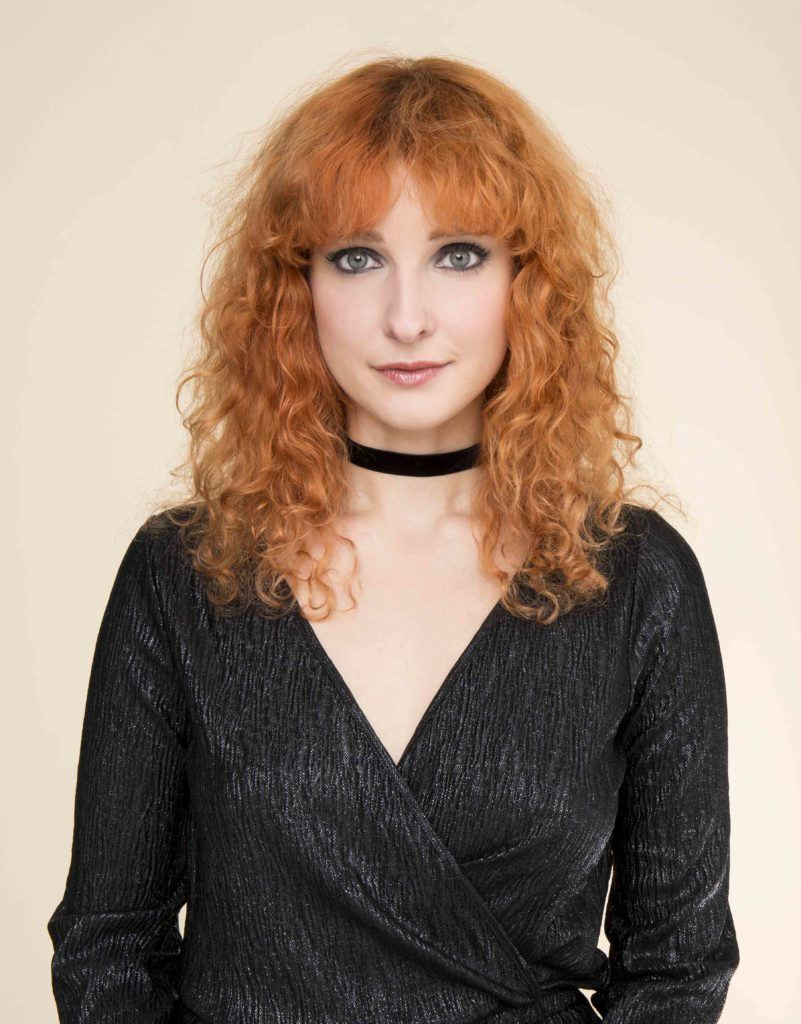 Party hairstyles: Woman with ginger fluffy curly medium length hair with bangs wearing a black wrap top and choker.